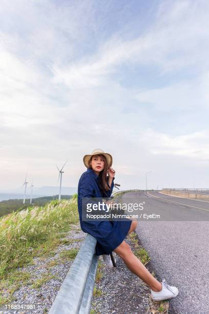 full length of woman leaning over crash barrier by road against sky - もたれる ストックフォトと画像