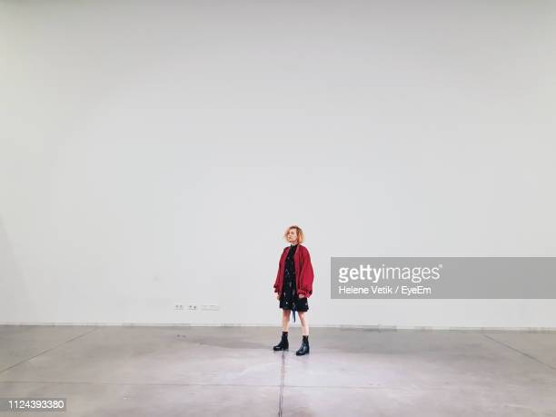 full length of woman looking away while standing against white wall - galleria d'arte foto e immagini stock