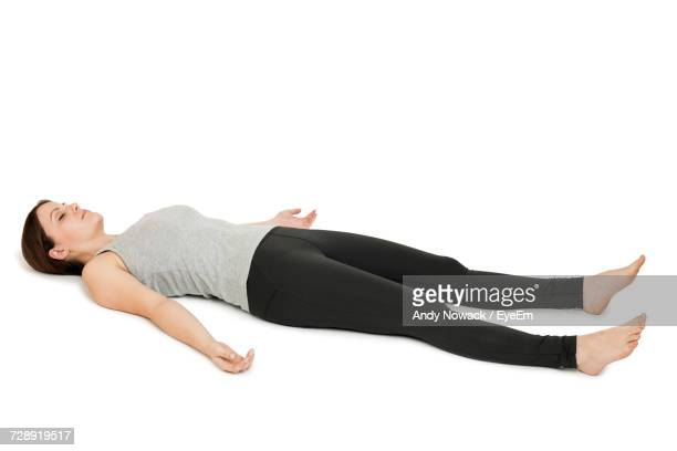 full length of woman lying against white background - lying on back stock pictures, royalty-free photos & images