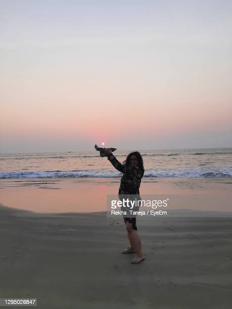 full length of woman on beach against sky during sunset - rekha stock pictures, royalty-free photos & images