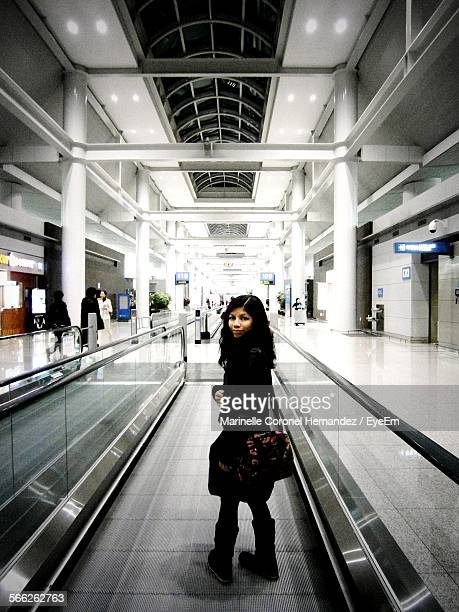 full length of woman on moving walkway at airport - incheon airport stock photos and pictures