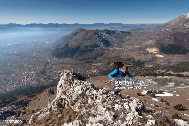 full length of woman on rocks against mountains - andrea rizzi foto e immagini stock