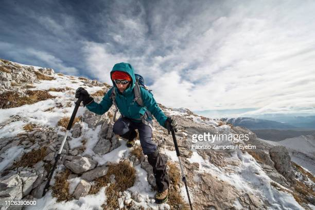 full length of woman on snowcapped mountain against sky during winter - fabrizio zampetti foto e immagini stock