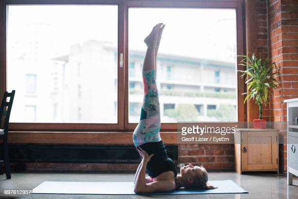 full length of woman performing shoulder stand by window at home - self improvement stock pictures, royalty-free photos & images