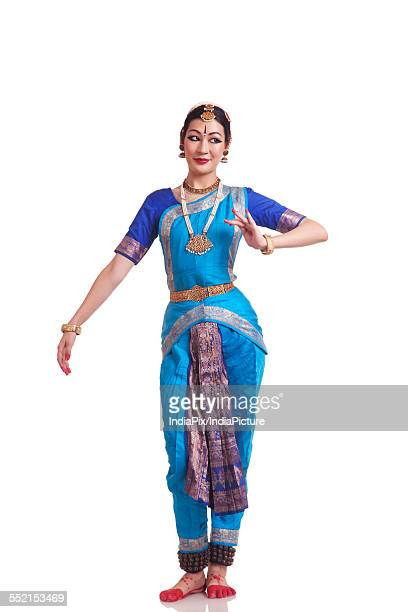 Full length of Woman performing traditional Bharat Natyam dance on white background