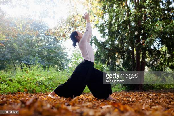 Full length of woman performing yoga while standing by trees at park during autumn