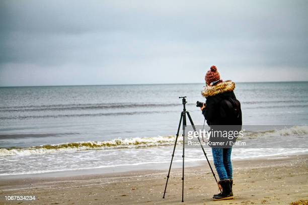 full length of woman photographing sea against sky - 三脚 ストックフォトと画像