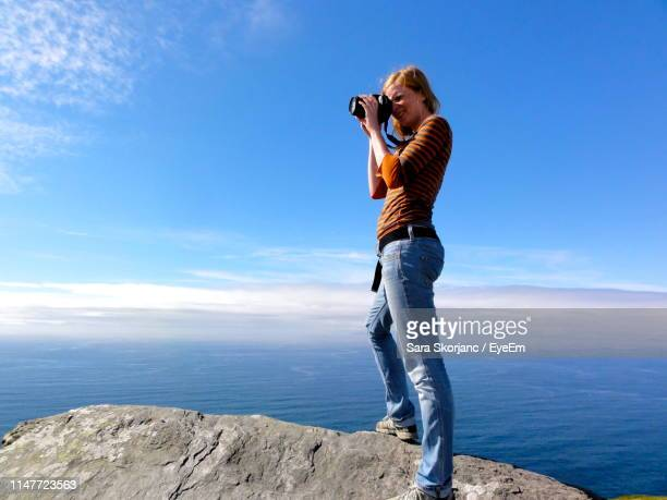 full length of woman photographing standing on cliff by sea against sky - photographer stock pictures, royalty-free photos & images