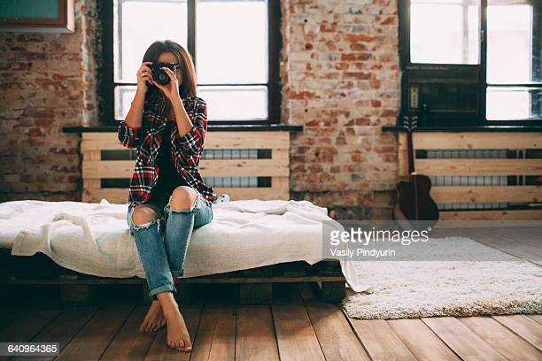 Full length of woman photographing through SLR camera in bedroom at home