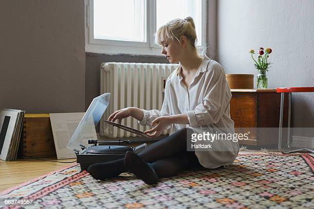Full length of woman playing record while sitting at home