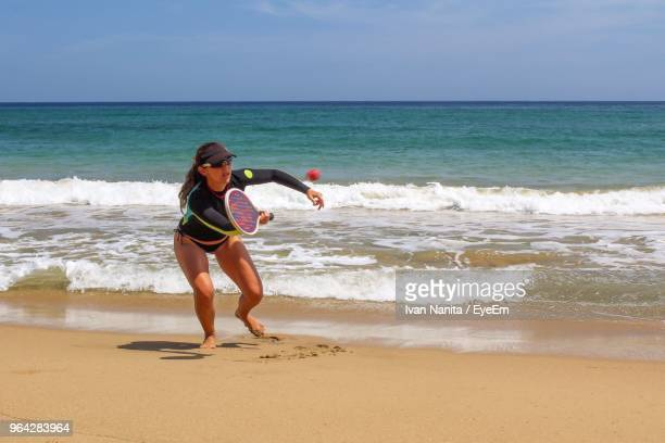 Full Length Of Woman Playing Tennis At Beach Against Sky