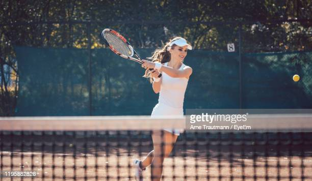 full length of woman playing tennis in court - tennis stock pictures, royalty-free photos & images