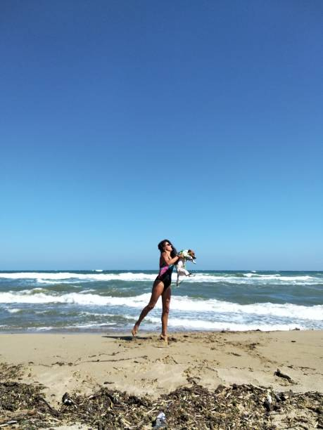 Full Length Of Woman Playing With Dog On Shore At Beach Against Clear Blue Sky