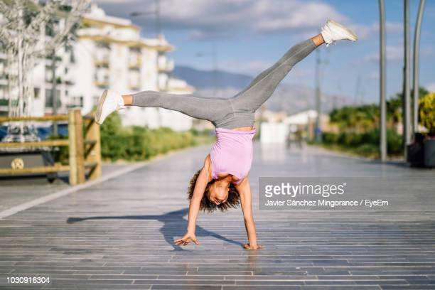 full length of woman practicing cartwheel on footpath in city - cartwheel stock pictures, royalty-free photos & images