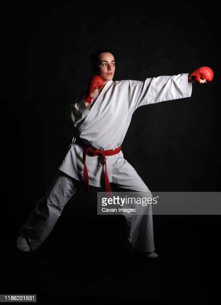 full length of woman practicing karate against black background - boxing belt stock pictures, royalty-free photos & images