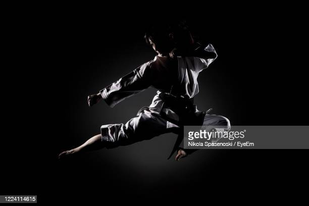 full length of woman practicing karate against black background - combat sport stock pictures, royalty-free photos & images
