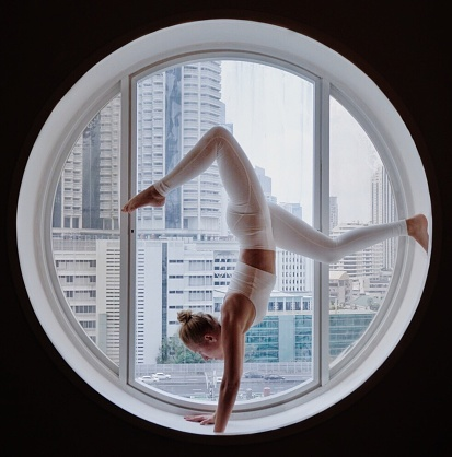 Full Length Of Woman Practicing Yoga At Circular Window - gettyimageskorea