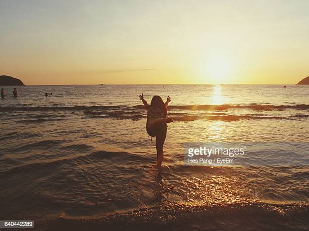 Full Length Of Woman Practicing Yoga In Shallow Water At Sea During Sunset