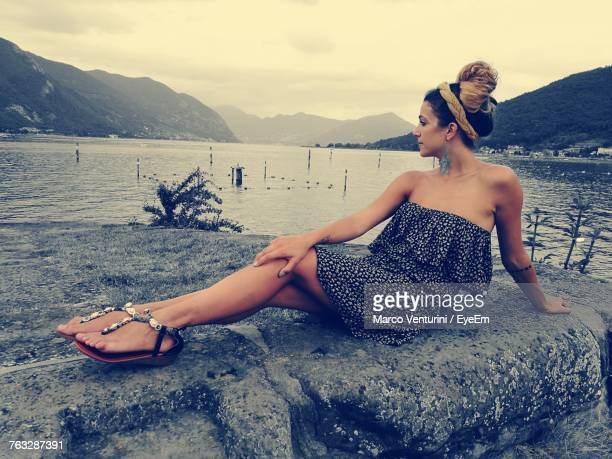 Full Length Of Woman Relaxing On Rock Against Sea And Sky