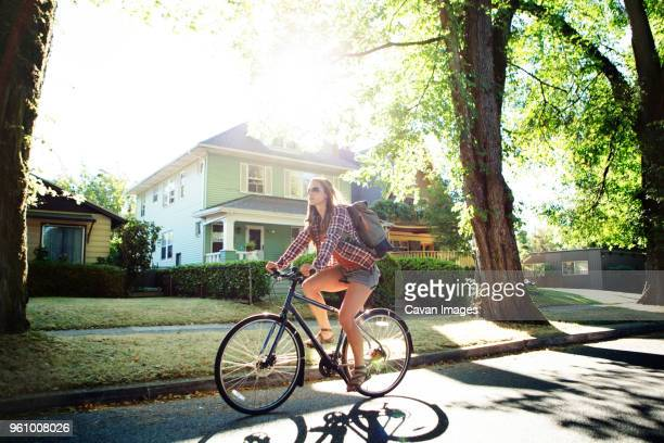 full length of woman riding bicycle on street during summer - portland oregon stock pictures, royalty-free photos & images