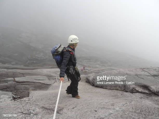 Full Length Of Woman Rock Climbing During Foggy Weather