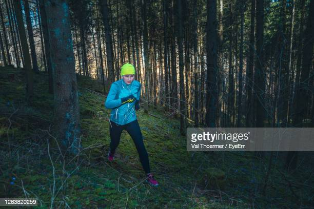 full length of woman running in forest - val thoermer stock-fotos und bilder
