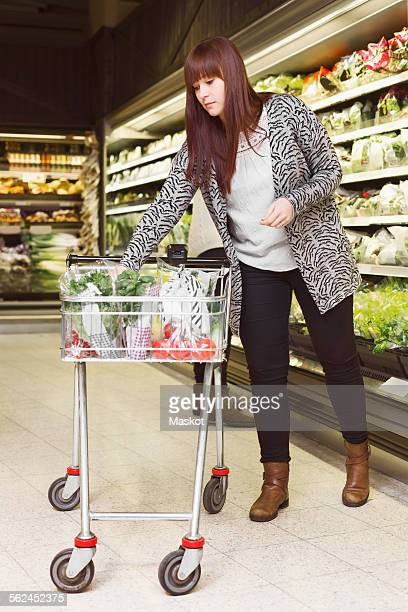 Full length of woman shopping groceries in supermarket