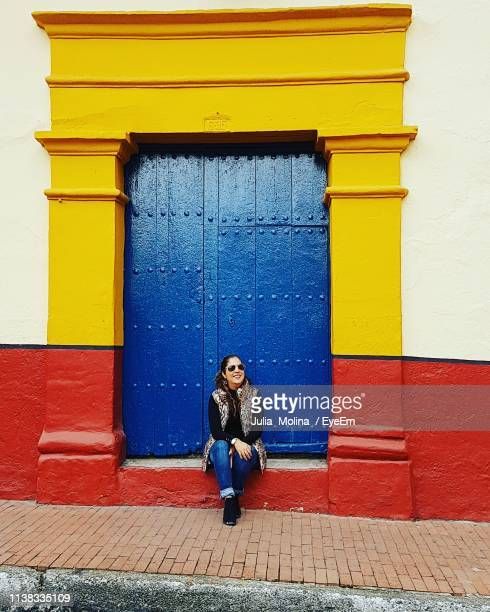 full length of woman sitting against colorful building in town - ボゴタ ストックフォトと画像