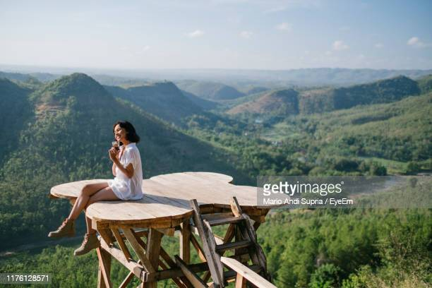 full length of woman sitting at observation point against mountains and sky - yogyakarta stock pictures, royalty-free photos & images