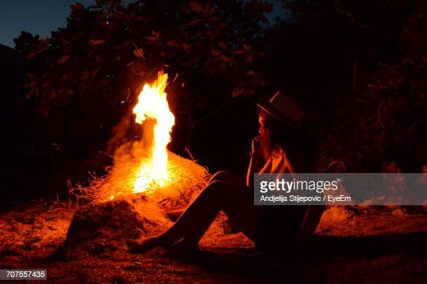 Full Length Of Woman Sitting By Bonfire At Beach During Night