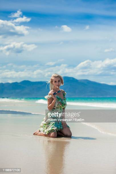 full length of woman sitting on beach against sky - ruben vardanyan stock pictures, royalty-free photos & images