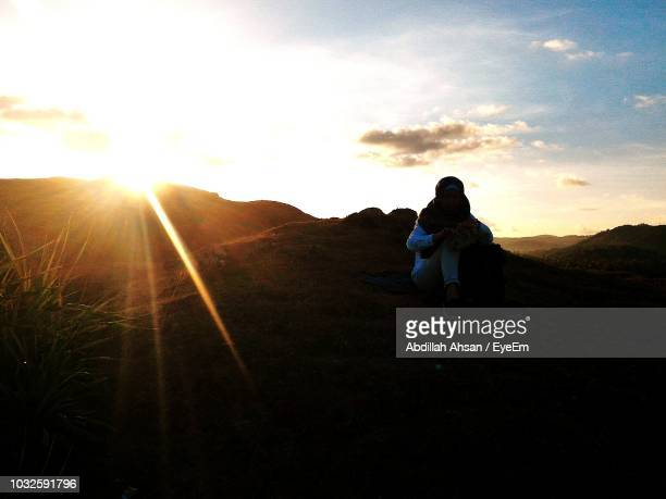 Full Length Of Woman Sitting On Hill