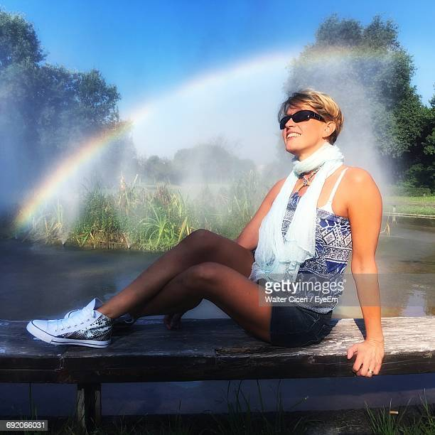 full length of woman sitting on park bench by lake against rainbow - walter ciceri foto e immagini stock