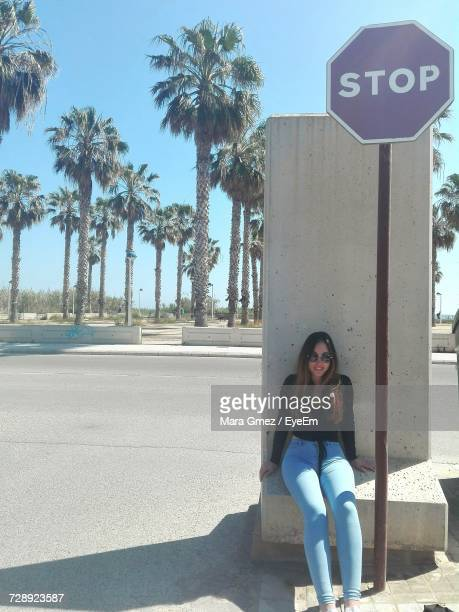 Full Length Of Woman Sitting On Retaining Wall By Stop Sign Against Palm Trees