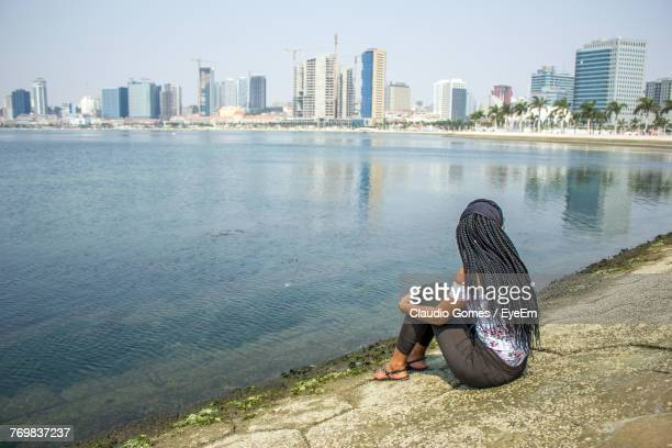 Full Length Of Woman Sitting On Riverbank In City Against Sky
