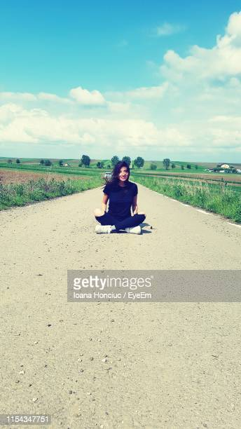 full length of woman sitting on road against sky - botoșani romania stock pictures, royalty-free photos & images
