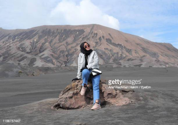 full length of woman sitting on rock against mountain - tengger stock pictures, royalty-free photos & images
