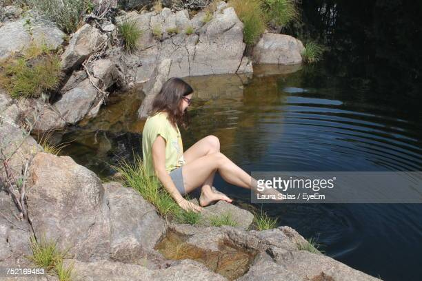 Full Length Of Woman Sitting On Rock By Lake
