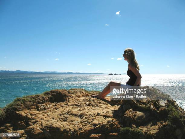 full length of woman sitting on rocks at sea against sky - klein stock pictures, royalty-free photos & images