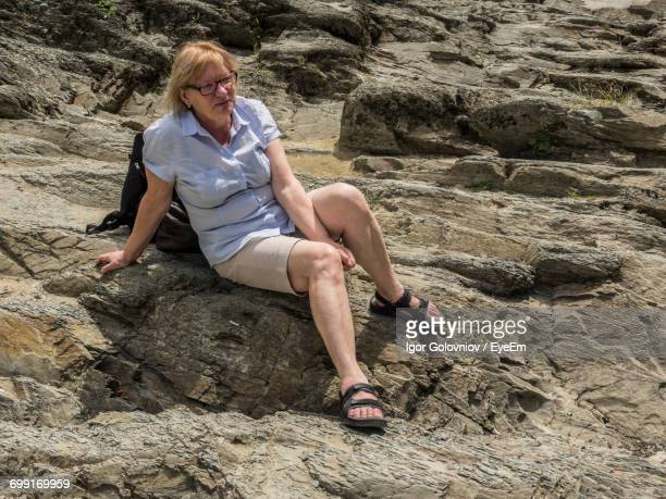 full length of woman sitting on rocks - igor golovniov stock pictures, royalty-free photos & images