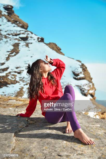 full length of woman sitting on rocky mountain - shimla stock pictures, royalty-free photos & images