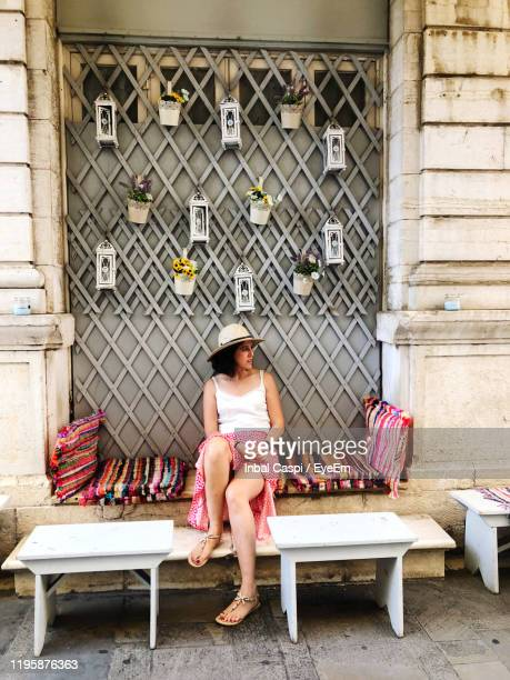 full length of woman sitting on seat - corfu stock pictures, royalty-free photos & images