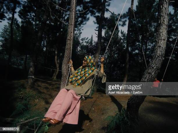 Full Length Of Woman Sitting On Swing