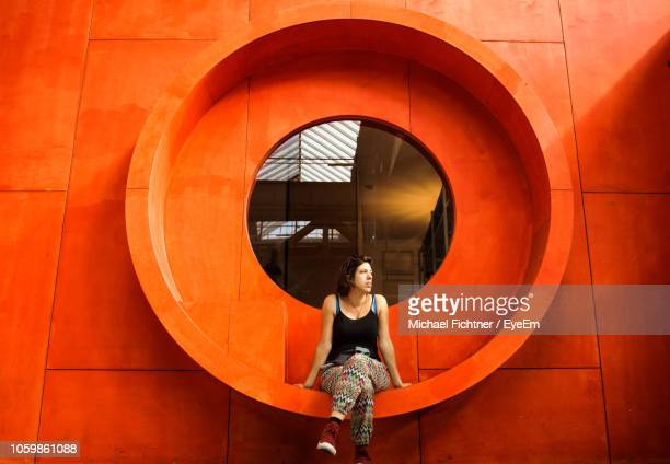 full length of woman sitting on window of orange building - circle stock pictures, royalty-free photos & images