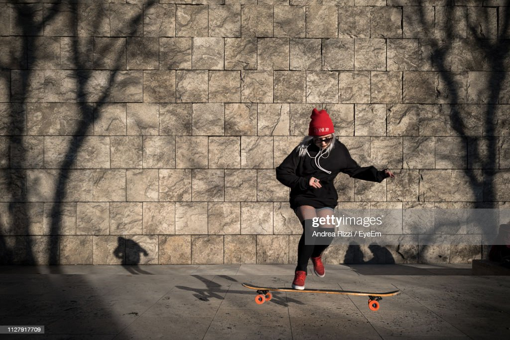 Full Length Of Woman Skateboarding On Footpath Against Wall : Foto stock