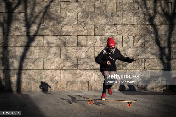 full length of woman skateboarding on footpath against wall - andrea rizzi foto e immagini stock