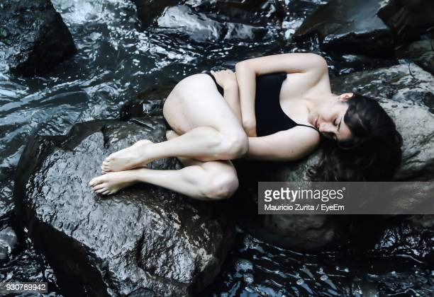 Full Length Of Woman Sleeping On Rocks At Beach