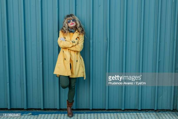 full length of woman standing against blue wall - coat stock pictures, royalty-free photos & images