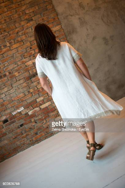 Full Length Of Woman Standing Against Brick Wall