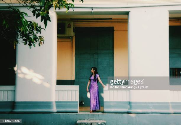 full length of woman standing against building - ko ko htike aung stock pictures, royalty-free photos & images